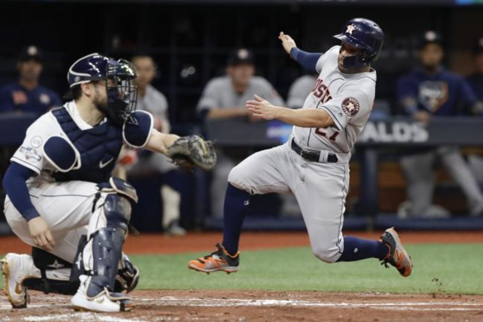 Photo -  Houston Astros' Jose Altuve, right, heads for home, but is tagged out by Tampa Bay Rays catcher Travis d'Arnaud during the fourth inning of Game 4 of the American League Division Series on Tuesday night in St. Petersburg, Fla. The Rays won 4-1 to force Game 5. [AP Photo/Chris O'Meara]