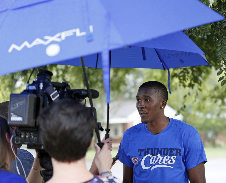 Photo - Oklahoma City guard Semaj Christon gives an interview in the rain during a stop by the Oklahoma City Thunder's Rolling Thunder Book Bus at Sequoyah Elementary, 2400 NW 36th St., in Oklahoma City, Thursday, Sept. 15, 2016. Photo by Nate Billings, The Oklahoman