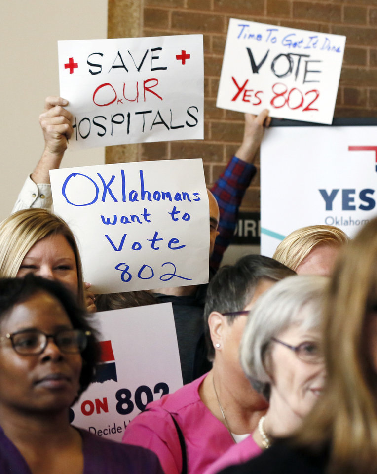 Photo - Supporters of Medicaid expansion hold signs before delivering petitions for state question 802 to the Oklahoma Secretary of State's office in Oklahoma City, Thursday, Oct. 24, 2019. [Nate Billings/The Oklahoman]