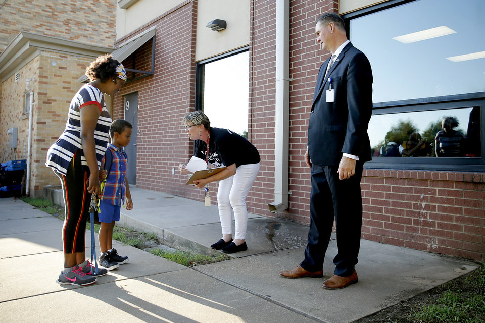 Photo - Principal Susan Carlsen greets Naaol Mulumhan, 5, and his mother Kiya for his first day of kindergarten beside Oklahoma City Public Schools Superintendent Sean McDaniel outside Britton Elementary in Oklahoma City, Monday, Aug. 12, 2019. [Bryan Terry/The Oklahoman]