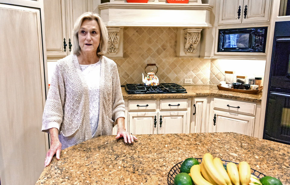Photo -  Beverly Hamilton, an agent with Metro First Realty, shows the kitchen of a home at 2800 Chaumont in Edmond that she has listed for $895,000. [PHOTO BY CHRIS LANDSBERGER, THE OKLAHOMAN]