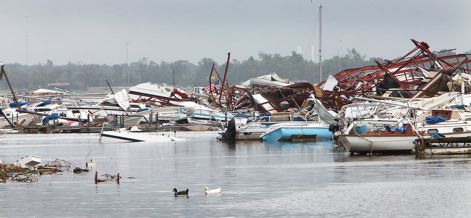 Photo - Ducks swim Tuesday by the boats damaged by the tornado at the marina at Lake Thunderbird State Park in Norman. Photo by David McDaniel, The Oklahoman
