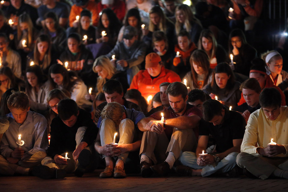 Photo - Students pray for the victims of the Oklahoma State University homecoming fatality car wreck during a candle light vigil on the campus of Oklahoma State Univeristy,  Sunday, Oct. 25, 2015. Photo by Sarah Phipps, The Oklahoman