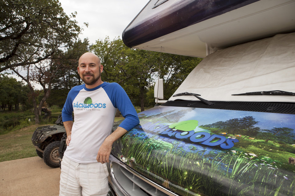 Photo -  Florida resident Will Royall stands next to his Backwoods-wrapped camp vehicle. He spends roughly a month in Oklahoma preparing for the Backwoods Camping and Music Festival. [Photo by Nathan Poppe, The Oklahoman]