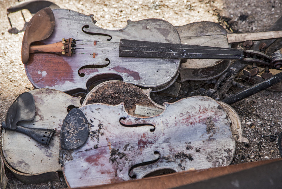 Photo - Items pull from the rubble of fiddle player Byron Berline's fiddle shop that was destroyed from a fire in Guthrie, Okla. on Monday, Feb. 25, 2019. The fire on Saturday destroyed two businesses in historic downtown Guthrie.   Photo by Chris Landsberger, The Oklahoman