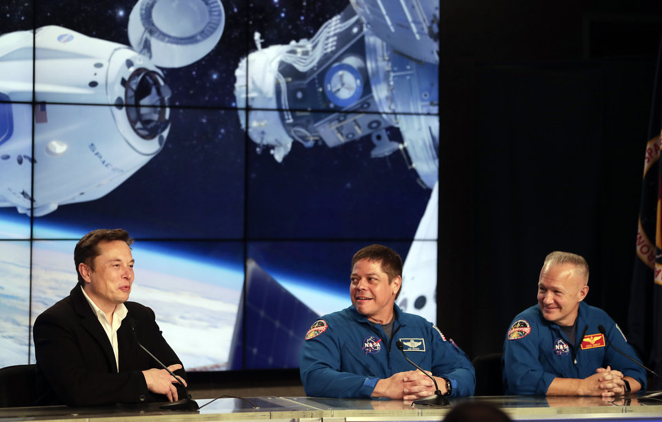 Photo -  FILE - In this Saturday, March 2, 2019 file photo, Elon Musk, left, CEO of SpaceX, speaks accompanied by NASA astronauts Bob Behnken, center, and Doug Hurley during a news conference after the SpaceX Falcon 9 Demo-1 launch at the Kennedy Space Center in Cape Canaveral, Fla. (AP Photo/John Raoux)
