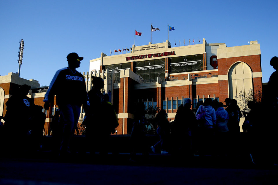 Photo - Fans walk past the stadium before an NCAA football game between the University of Oklahoma Sooners (OU) and the Iowa State University Cyclones at Gaylord Family-Oklahoma Memorial Stadium in Norman, Okla., Saturday, Nov. 9, 2019. [Bryan Terry/The Oklahoman]