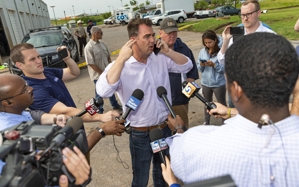 Photo - Gov. Kevin Stitt talks to President Donald Trump on the phone as Stitt tours the aftermath of a tornado in El Reno, Okla. on Monday, May 27, 2019. The EF3 tornado hit the American Budget Value Inn and Skyview Mobile Home Park on Saturday night killing two people and injuring many others. [Chris Landsberger/The Oklahoman]