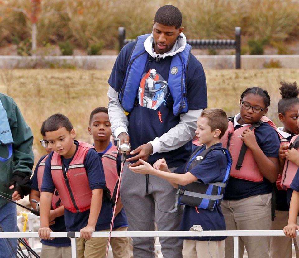 Photo - Paul George helped teach fourth-grade students how to cast a line at Monday's launch of his outdoor initiative for kids. [PHOTO BY STEVE SISNEY, THE OKLAHOMAN]