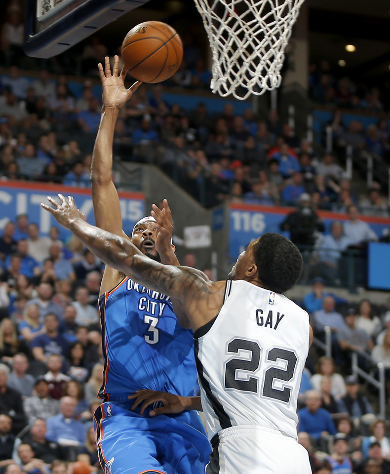 Photo -  Oklahoma City's Corey Brewer goes to the basket beside San Antonio's Rudy Gay during Saturday's game at Chesapeake Energy Arena. [Photo by Bryan Terry, The Oklahoman]
