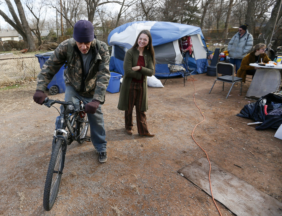 Photo - Jamie Zumwalt, 51, founder and pastor of Joe's Addiction, middle, smiles as Sammy Edwards, 55, leaves on his bicycle after he dropped by to say hello where lunch was being served out of a tent at 6100 S Cox, near the original location of Joe's Addiction, in Valley Brook, Okla., Monday, Dec. 23, 2019. While the new site for Joe's Addiction is not ready, Zumwalt continues to help the community of people in need who were being served by Joe's Addiction. [Nate Billings/The Oklahoman]
