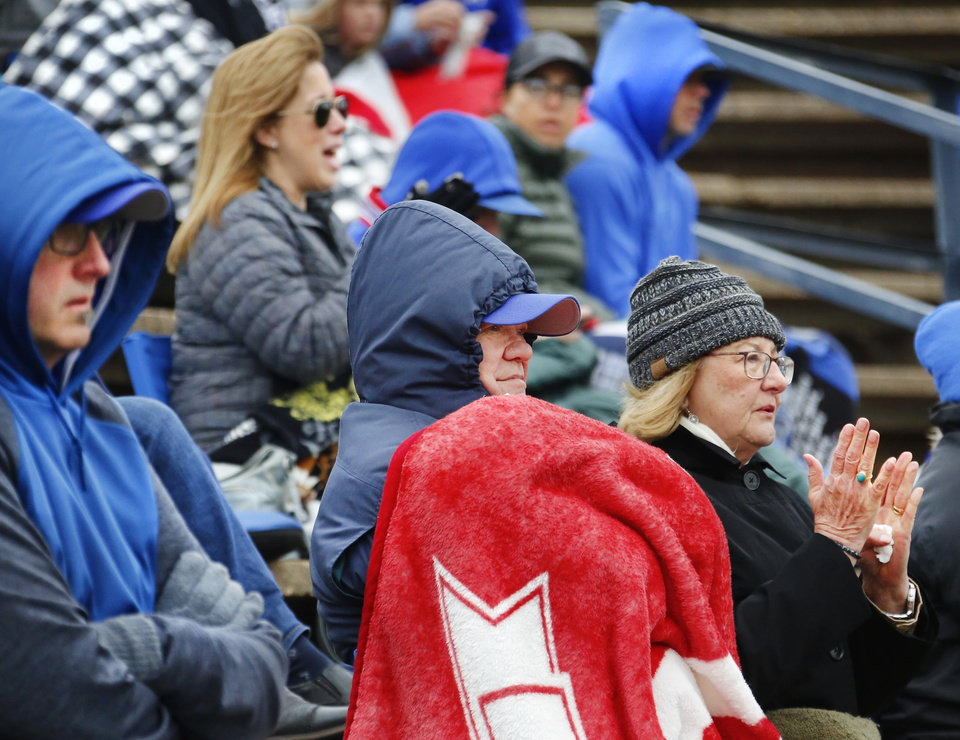 Photo - Fans of Christian Heritage Academy baseball team are bundled against unseasonably cool temperatures and northerly winds as they watch their players compete against Dale Pirates during the Class 2A state quarterfinal game at Shawnee High School Thursday, May 9, 2019. Dale advances to the next round of playoffs, defeating Christian Heritage, 11-0.   [Jim Beckel/The Oklahoman]