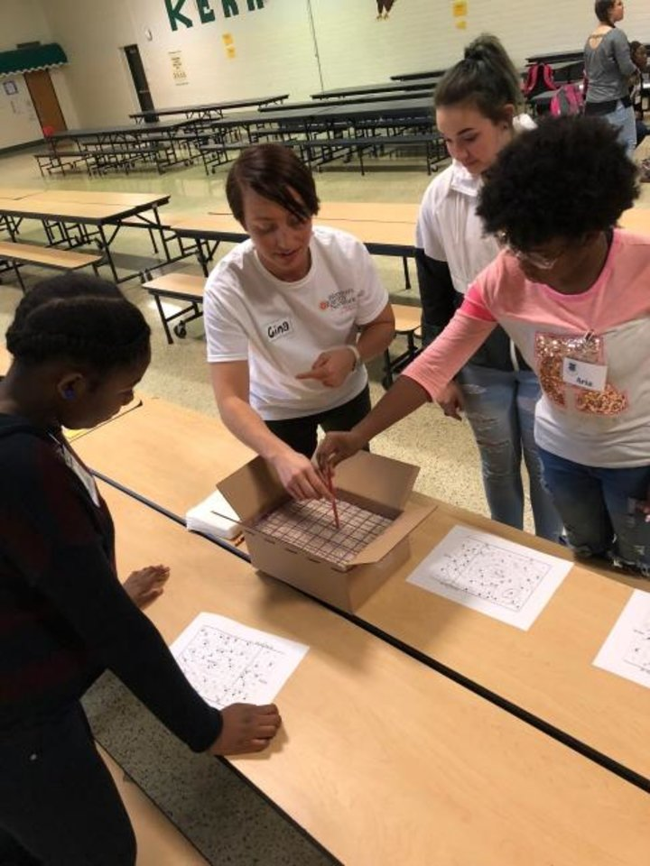 Photo -  A member of the Greater Oklahoma chapter of Women's Energy Network works with students taking part in a recent STARBASE Oklahoma class. The program aims to get diverse youths interested in careers involving science, technology, engineering and math.