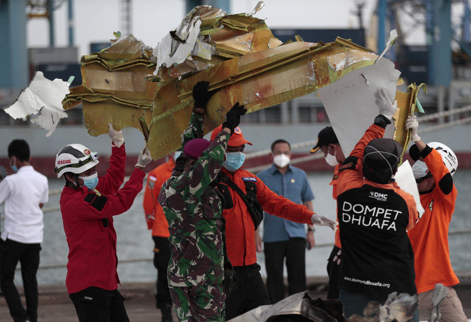 Photo -  Rescuers carry a part of aircraft recovered from Java Sea where a Sriwijaya Air passenger jet crashed, at Tanjung Priok Port in Jakarta, Indonesia, Monday, Jan. 11, 2021. The search for the black boxes of a crashed Sriwijaya Air jet intensified Monday to boost the investigation into what caused the plane carrying dozens of people to nosedive at high velocity into the Java Sea. (AP Photo/Dita Alangkara)