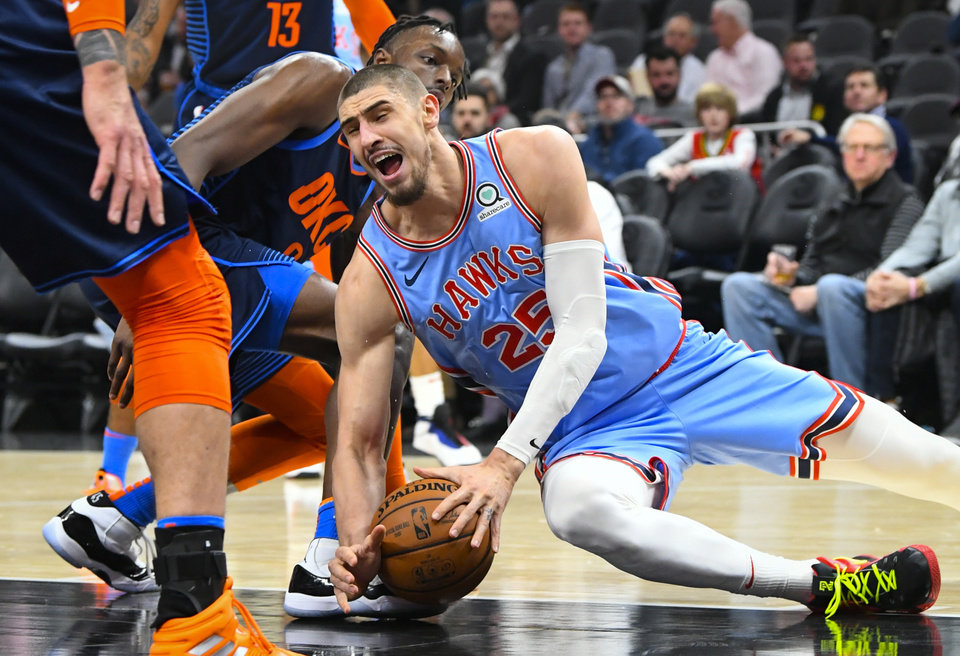Photo - Atlanta Hawks center Alex Len (25) goes down for a loose ball in front of Oklahoma City Thunder forward Jerami Grant during the second half of an NBA basketball game, Tuesday, Jan. 15, 2019, in Atlanta. (AP Photo/John Amis)