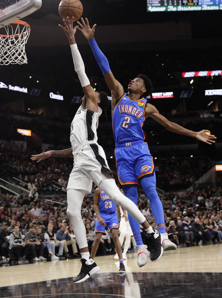 Photo - Oklahoma City Thunder guard Shai Gilgeous-Alexander (2) blocks San Antonio Spurs guard Dejounte Murray (5) as he tries to score during the second half of an NBA basketball game, in San Antonio, Thursday, Jan. 2, 2020. Oklahoma City won 109-103. (AP Photo/Eric Gay)