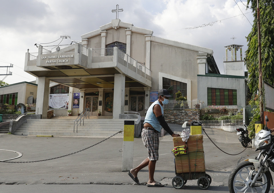 Photo -  A vendor wearing a protective mask walks past a church in suburban Quezon city, in Manila, Philipines on Saturday March 14, 2020. Masses at churches in metropolitan Manila have been suspended as a precautionary measure against the spread of the new Coronavirus. Philippine officials on Saturday declared a night curfew in the capital and said millions of people in the densely populated region could only go out of their homes for work, buy necessities and medical emergencies at daytime under a monthlong quarantine to be imposed to fight the new coronavirus. (AP Photo/Aaron Favila)