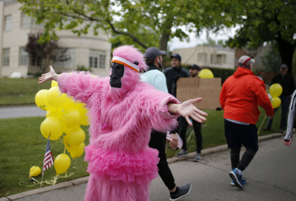 Photo - Susan Phillips dressed as a gorilla greets runners on Gorilla Hill during the 2017 Oklahoma City Memorial Marathon Sunday, April 30, 2017.  Photo by Sarah Phipps, The Oklahoman