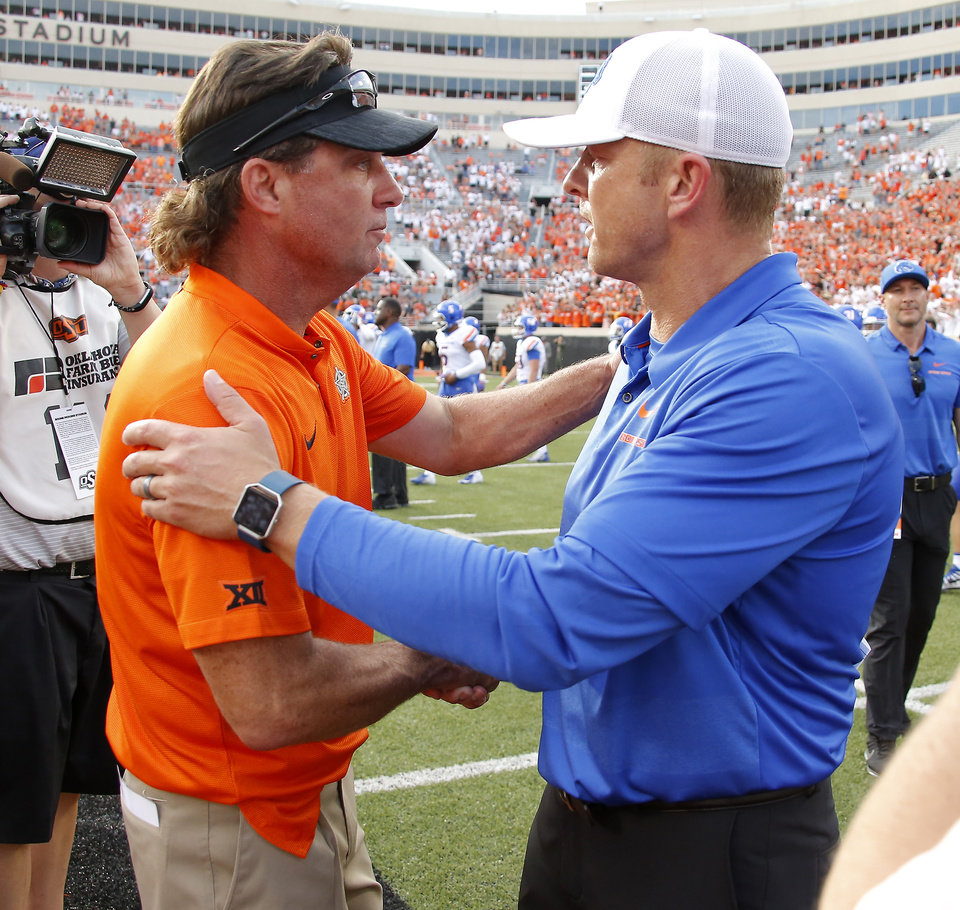 Photo - Oklahoma State coach Mike Gundy and Boise State coach Bryan Harsin shake hands  after a college football game between the Oklahoma State University Cowboys (OSU) and the Boise State Broncos at Boone Pickens Stadium in Stillwater, Okla., Saturday, Sept. 15, 2018. Oklahoma State won 44-21. Photo by Bryan Terry, The Oklahoman