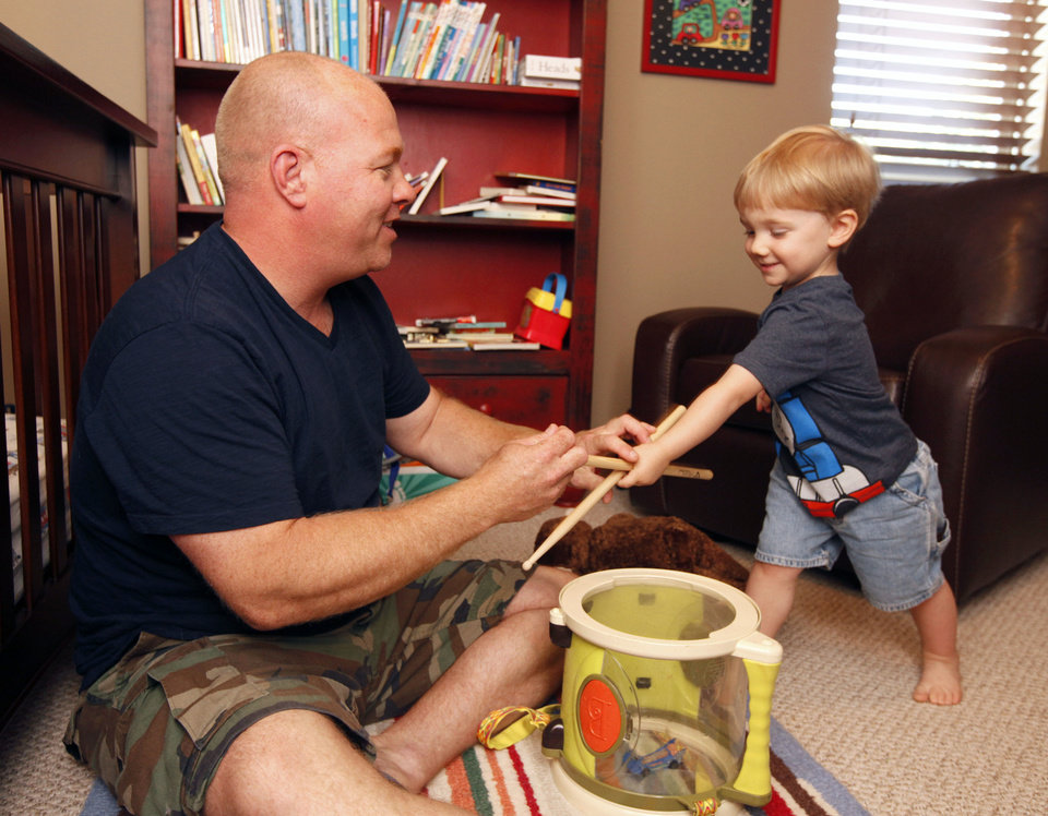 Photo - Andy Brooks plays Monday with his 2-year-old son, Ben, at their home in Edmond. Photo by Paul Hellstern, The Oklahoman  PAUL HELLSTERN