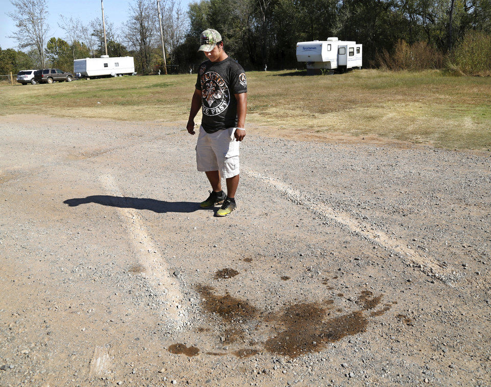 Photo - Johnathan Chouinard stands between two abrasions in a gravel road at Bear Creek mobile home community located south of SH 66 west of Wellston on Monday, Oct. 24, 2016. Chouinard said the marks were left when shooting suspect Michael Dale Vance pulled the stolen police vehicle he was driving and stopped abruptly in front of Chouinard and his wife, Jamie, Sunday night, blocking their path as they were coming home from dinner with family. Vance pointed a semi- automatic weapon at Chouinard and demanded he give him the couple's Lincoln Continental. The dark spots on the ground are a result of leaking engine fluids coming from the vehicle Vance was driving. 