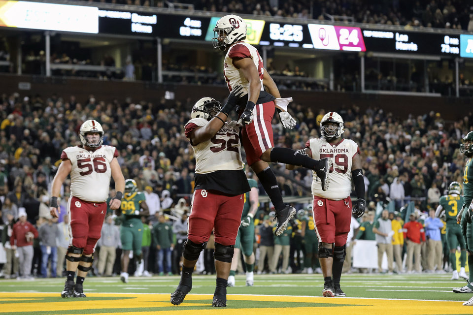 Photo - Oklahoma fullback Brayden Willis, center top, is lifted in the air by Oklahoma offensive lineman Tyrese Robinson, bottom center, after scoring a touchdown against Baylor during the second half of an NCAA college football game in Waco, Texas, Saturday, Nov. 16, 2019. Oklahoma won 34-31. (AP Photo/Ray Carlin)