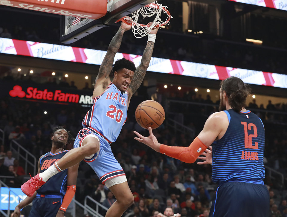 Photo -  Atlanta's John Collins dunks while Oklahoma City's Steven Adams looks on during Tuesday night's game at State Farm Arena in Atlanta. The Hawks whipped OKC, 142-126. [AP PHOTO]