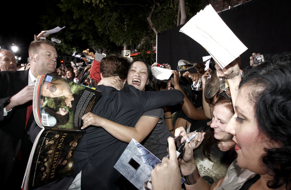 Photo - Actor Robert Pattinson hugs a fan as he arrives at The Twilight Saga: New Moon premiere in Westwood, Calif. Monday, Nov. 16, 2009.  (AP Photo/Matt Sayles) ORG XMIT: CAGS160