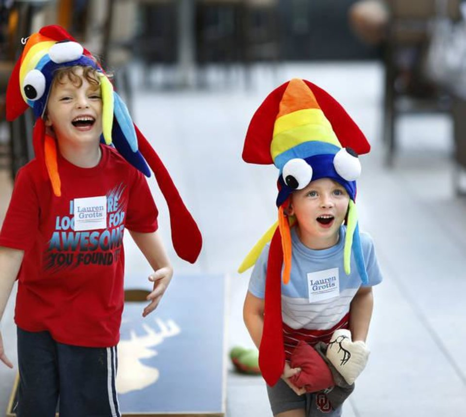 Photo -  Brothers Elijah, 6, and Caleb Grotts, 4, enjoy a game of cornhole Tuesday while accompanying their parents to a watch party on the patio of the Colcord Hotel in downtown Oklahoma City where a small group of medical marijuana supporters followed election results on television and electronic devices. These boys' mother, Lauren Grotts, was also keeping her attention focused on the House District 101 race, in which she was a candidate. [Photo by Jim Beckel, The Oklahoman]