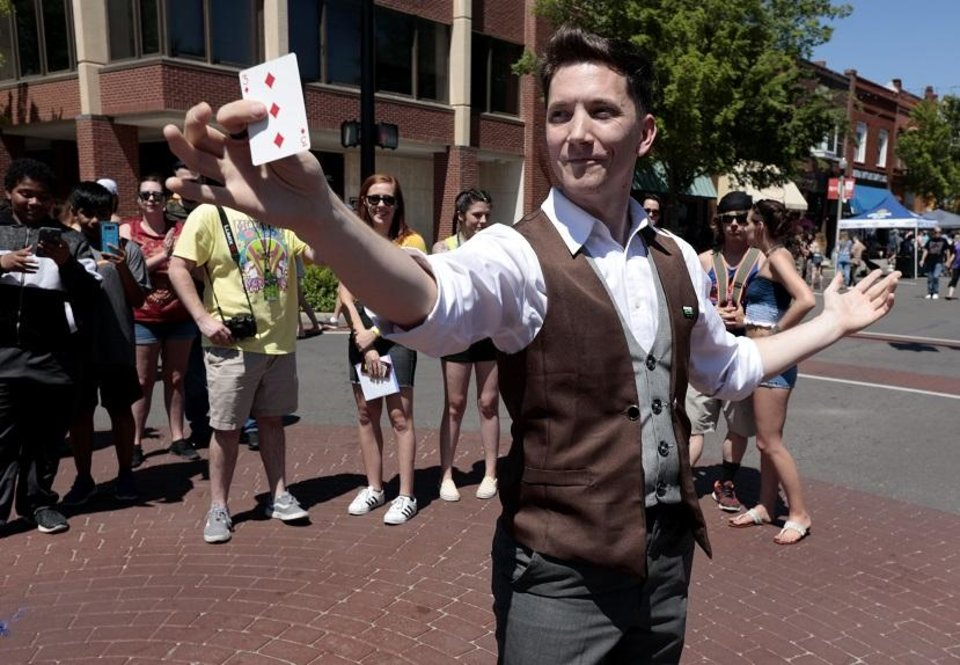 Photo - Magician Joe Coover performs a magic show in the middle of Main Street during Norman Music Festival 2019 on April 27, 2019 in Norman, Okla.  [Steve Sisney/For The Oklahoman]