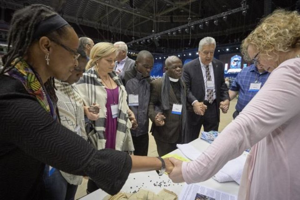 Photo -  Delegates pray together during the  opening session of the 2019 General Conference of the United Methodist Church in St. Louis. [Provided by United Methodist News Service]