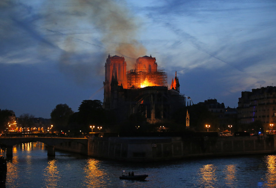 Photo - Firefighters tackle the blaze as flames and smoke rise from Notre Dame cathedral as it burns in Paris, Monday, April 15, 2019. Massive plumes of yellow brown smoke is filling the air above Notre Dame Cathedral and ash is falling on tourists and others around the island that marks the center of Paris. (AP Photo/Michel Euler)