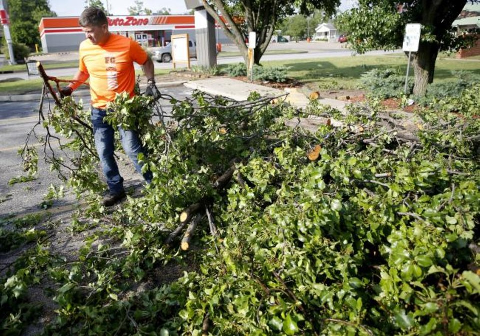 Photo -  The Rev. Tobin Jackson clears trees from the parking lot of Trinity Baptist Church on Sunday. [Sarah Phipps/The Oklahoman]
