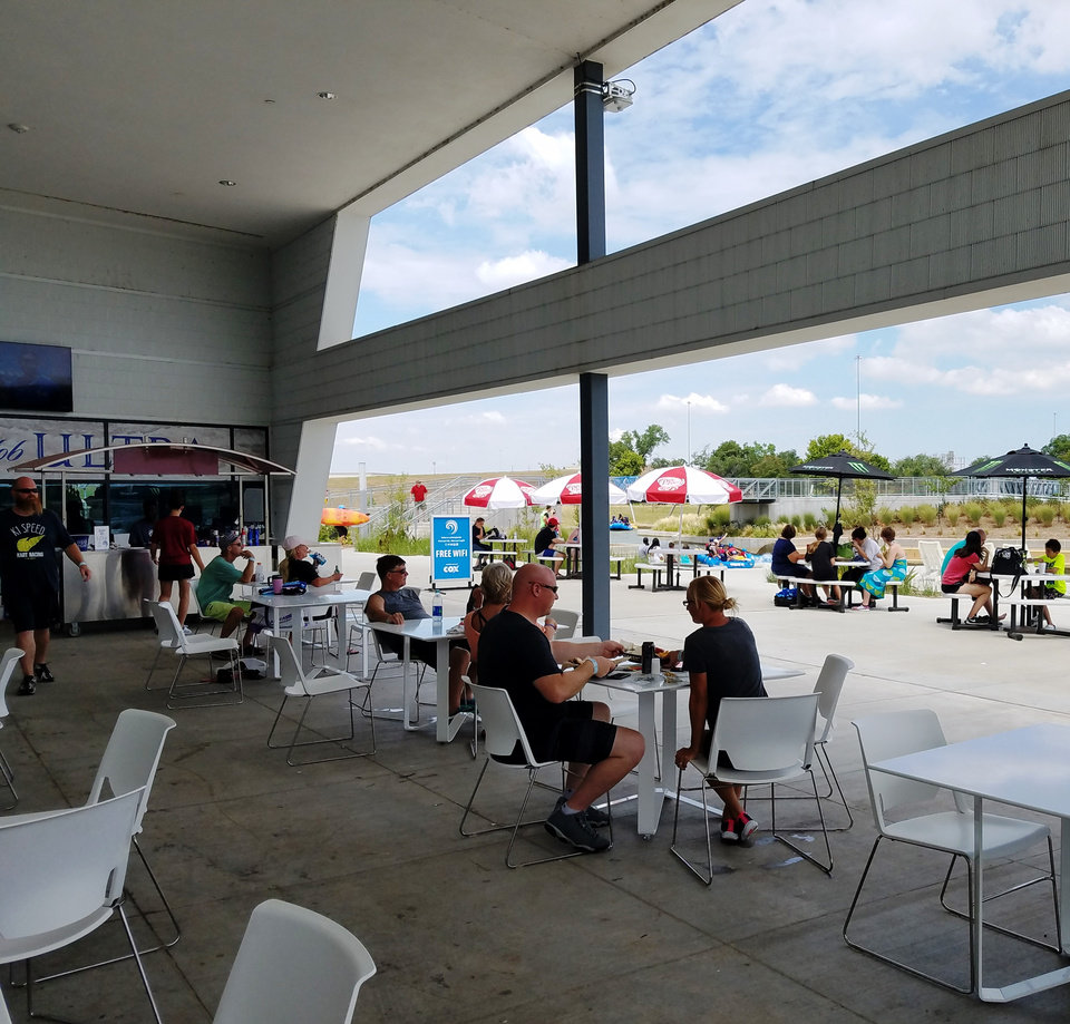 Photo -  Visitors have lunch Sunday on the patio of the white water center at Riversport Rapids along the Oklahoma River. [Photo by Steve Lackmeyer, The Oklahoman]