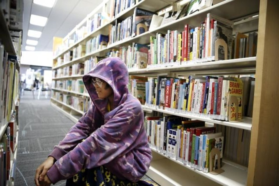 Photo -  Arrielle Toney looks for a book in the shelves at the Ralph Ellison Library, 2000 NE 23, in Oklahoma City, Friday, Feb. 7, 2020. [Nate Billings/The Oklahoman]