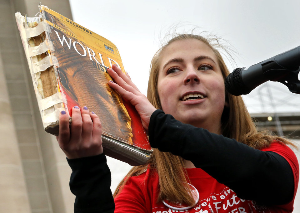 Photo -  Hope Davis, Moore High School sophomore, holds up her tattered history book as Oklahoma teachers hold a rally at the state Capitol on Monday. [Photo by Steve Sisney, The Oklahoman]