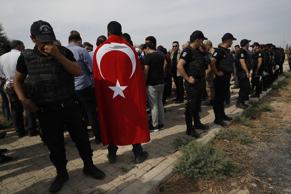 Photo -  Turkish police officers secure the area as a Turkish flag-draped mourner attends the funeral of ten-month-old Mohammed Omar Saar, killed during incoming shelling from Syria Thursday, in Akcakale, Sanliurfa province, southeastern Turkey, at the border with Syria, Friday, Oct. 11, 2019. (AP Photo/Lefteris Pitarakis)
