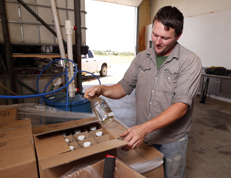 Photo -  Ricky Sowers boxes up moonshine Wednesday at his Okie Shine distillery in Tuttle. Sowers' company is the first legal distiller of moonshine in Oklahoma. [Photo by Steve Sisney, The Oklahoman]