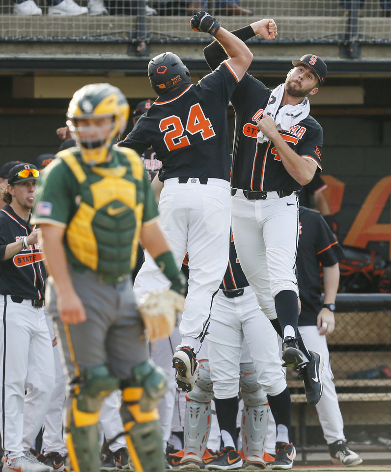 Photo - OSU's Joe Lienhard (46), right, and Colin Simpson (24) celebrate a home run by Simpson in the first inning near Baylor catcher Shea Langeliers (23) in the first inning during a college baseball game between Baylor and Oklahoma State in the last regular-season series at Allie P. Reynolds Stadium in Stillwater, Okla., Friday, May 17, 2019. [Nate Billings/The Oklahoman]