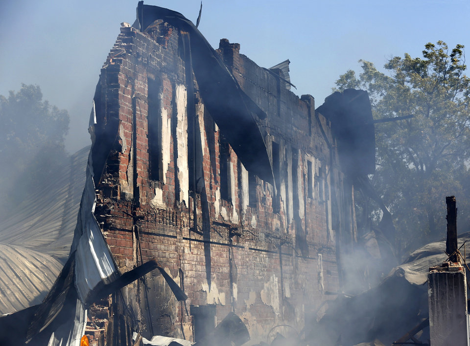 Photo -  A weekend fire in in downtown Seminole destroyed multiple historic brick buildings on Main Street. On Monday, smoke continued to rise from the twisted and charred rubble. [Photo by Jim Beckel, The Oklahoman]