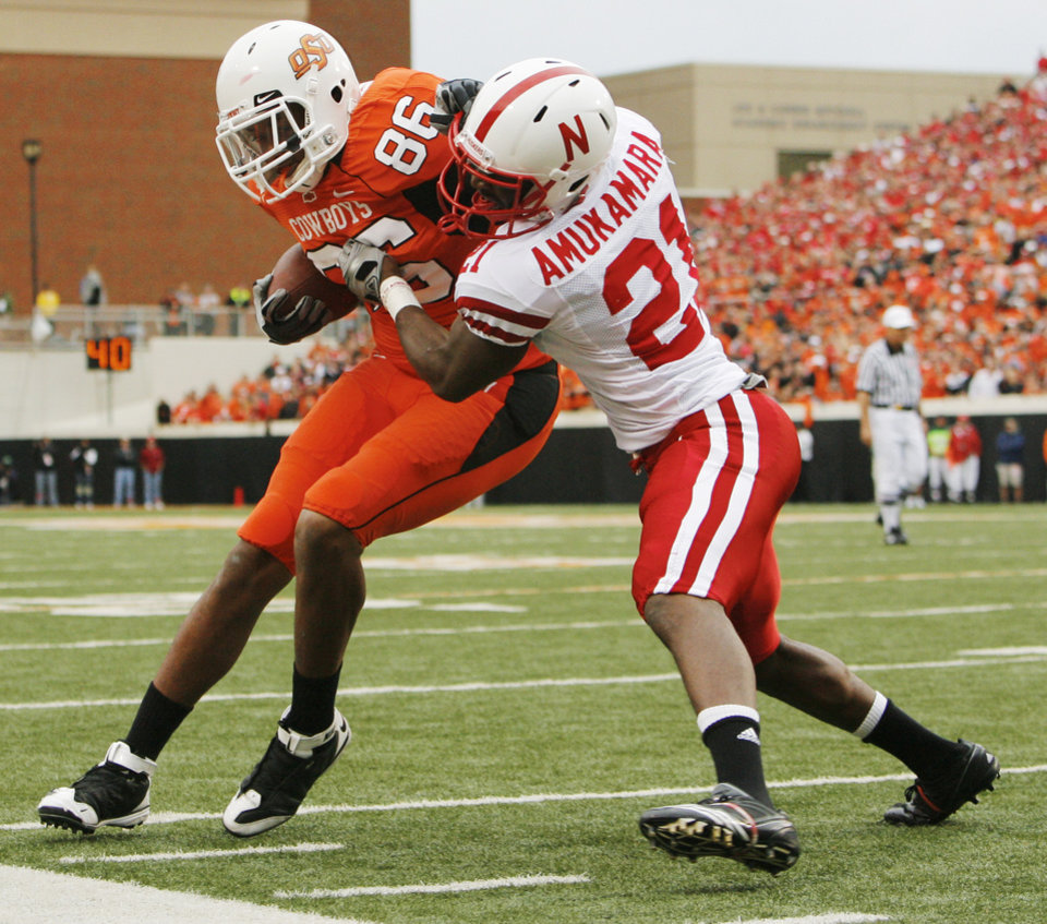 Photo - OSU's Wilson Youman (86) is stopped by Prince Amukamara (21) of Nebraska after making a catch in the first quarter during the college football game between the Oklahoma State Cowboys (OSU) and the Nebraska Huskers (NU) at Boone Pickens Stadium in Stillwater, Okla., Saturday, Oct. 23, 2010. Photo by Nate Billings, The Oklahoman