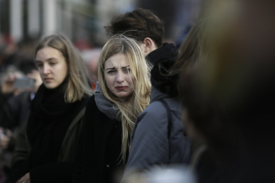 Photo - A woman cries as she mourns for the victims killed in the Friday's attacks in Paris, France, in front of the French Embassy in Berlin, Saturday, Nov. 14, 2015.  French President Francois Hollande said more than 120 people died Friday night in shootings at Paris cafes, suicide bombings near France's national stadium and a hostage-taking slaughter inside a concert hall. (AP Photo/Markus Schreiber)