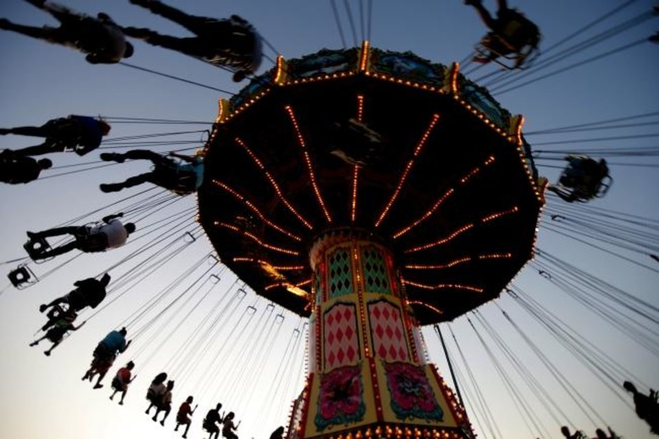 Photo -  As the sun sets at the OKC Fairgrounds, people enjoy a ride during the 2019 Oklahoma State Fair in Oklahoma City. This year's Oklahoma State Fair has been canceled. [Bryan Terry/The Oklahoman]