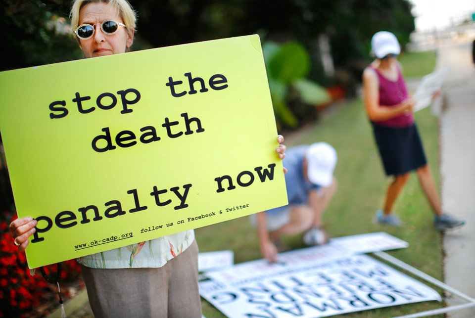 Photo - Karin Stafford, of Oklahoma City, joins a crowd of peaceful protestors who gathered along NE 23 Street in front of the Governor's Mansion in Oklahoma City on  Wednesday, Sep. 30, 2015, to keep a silent vigil as the scheduled time drew near for the execution of convicted killer Richard Glossip at the state penitentiary in McAlester. Stafford said this was the first time she has taken part in an anti-death penalty vigil.She came by herself, but stood shoulder to shoulder with other protestors.  As many as 40 people held banners, waved signs and waved as honking motorists passed during their nearly two-hour long vigil.  Several groups were represented among the protestors, including the Oklahoma Coalition to Abolish the Death Penalty, The Norman community of Quakers and Amnesty International. Glossip, 52, received a last minute stay from Gov. Mary Fallin. He was scheduled to to die at 3 p.m. Wednesday after being convicted in two separate trials in the 1997 beating death of his boss, Barry Van Treese. Photo by Jim Beckel, The Oklahoman.