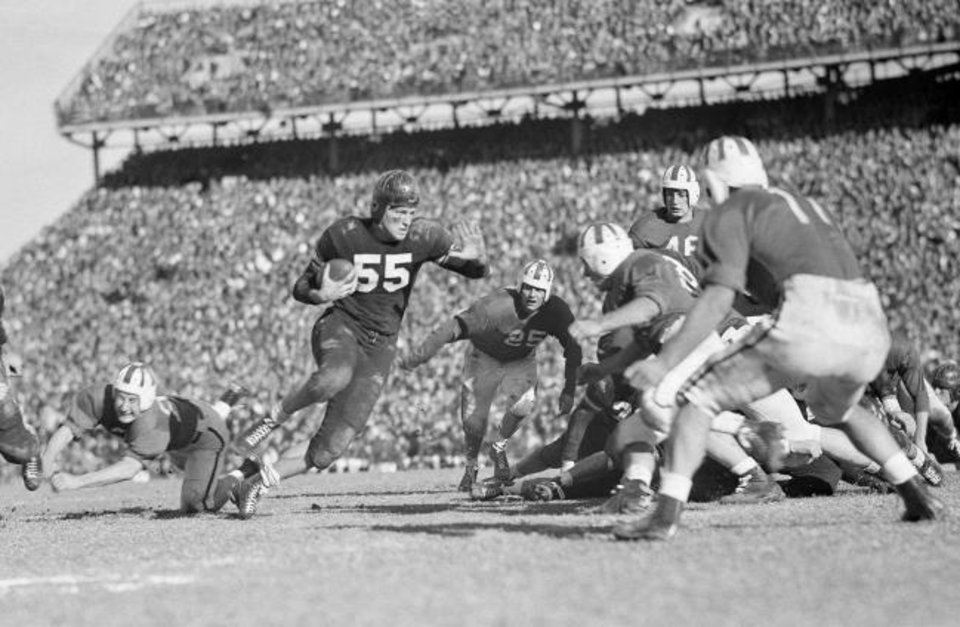 Photo -  Oklahoma A&M's Bob Fenimore (55) stiff arms his way through the Saint Mary defense during Oklahoma A&M's Sugar Bowl win Jan. 1, 1946, in New Orleans. The then-Aggies went undefeated in the 1945 season and were retroactively awarded the national title in 2016. [AP Photo/File]