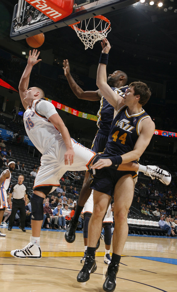 Photo - Oklahoma City's Cole Aldrich shoots in front of Utah's Kyrylo Fesenko during the NBA basketball game between the Oklahoma City Thunder and Utah Jazz in the Oklahoma City Arena on Sunday, Oct. 31, 2010. Photo by Sarah Phipps, The Oklahoman