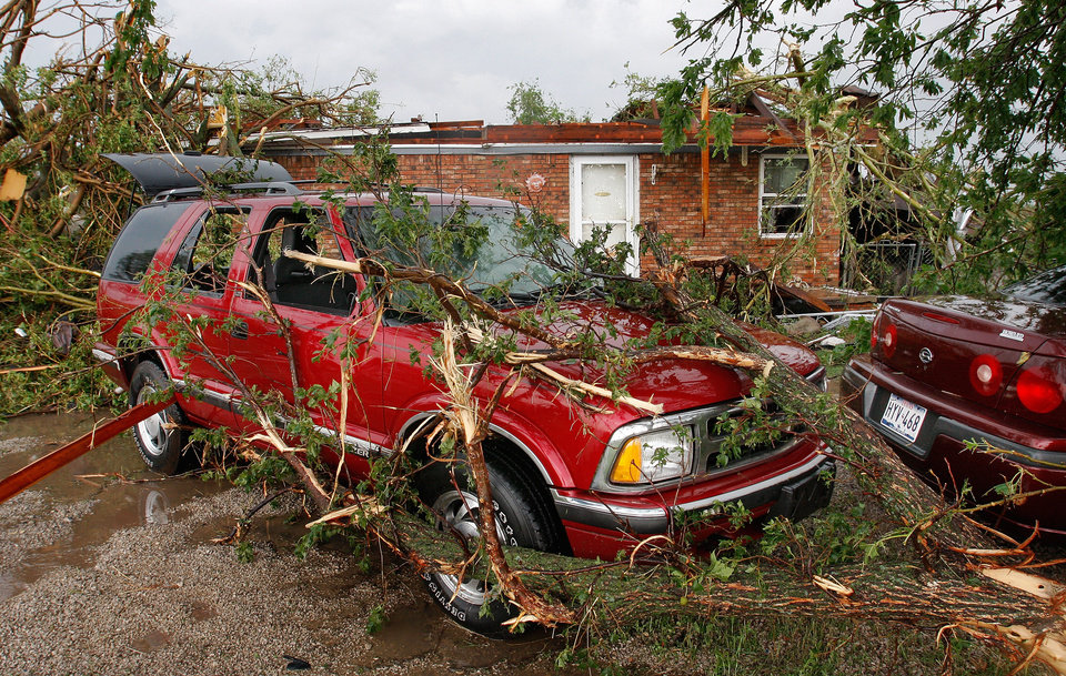 Photo - Tree branches cover  cars in the driveway of a home on SH 74F near Cashion after a tornado raced across Logan County  Tuesday afternoon,  May 24, 2011,   The home's roof was pulled away and more than a dozen trees on the property were knocked down. Photo by Jim Beckel, The Oklahoman