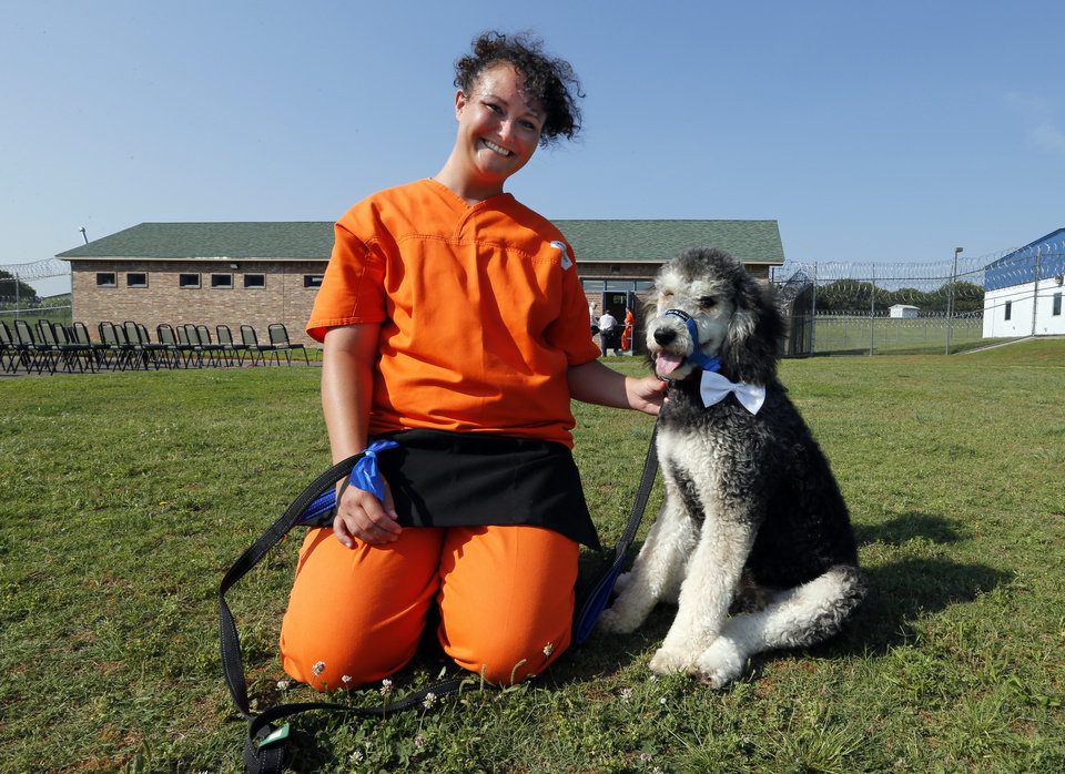 Photo -  Lacey Wallace works with her dog in training McAlister at the opening of a new dog training facility at Mabel Basset Correctional Center in McLoud. [Photo by Steve Sisney, The Oklahoman]