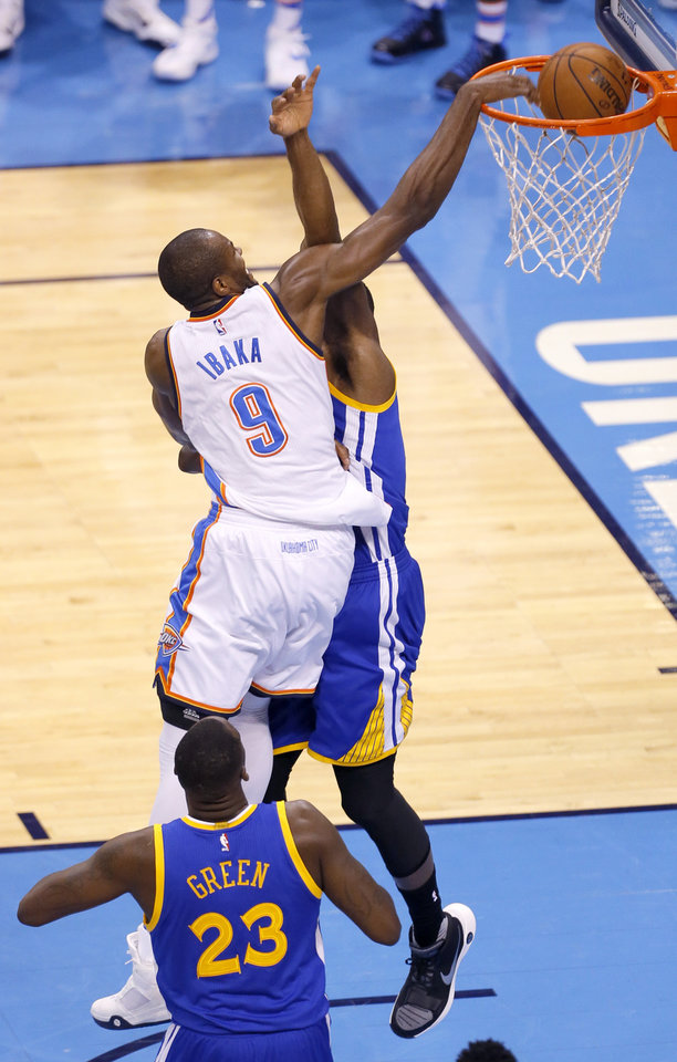 Photo - Oklahoma City's Serge Ibaka (9) dunks the ball over Golden State 's Festus Ezeli (31) as Draymond Green (23)  looks on during Game 3 of the Western Conference finals in the NBA playoffs between the Oklahoma City Thunder and the Golden State Warriors at Chesapeake Energy Arena in Oklahoma City, Sunday, May 22, 2016. Photo by Sarah Phipps, The Oklahoman