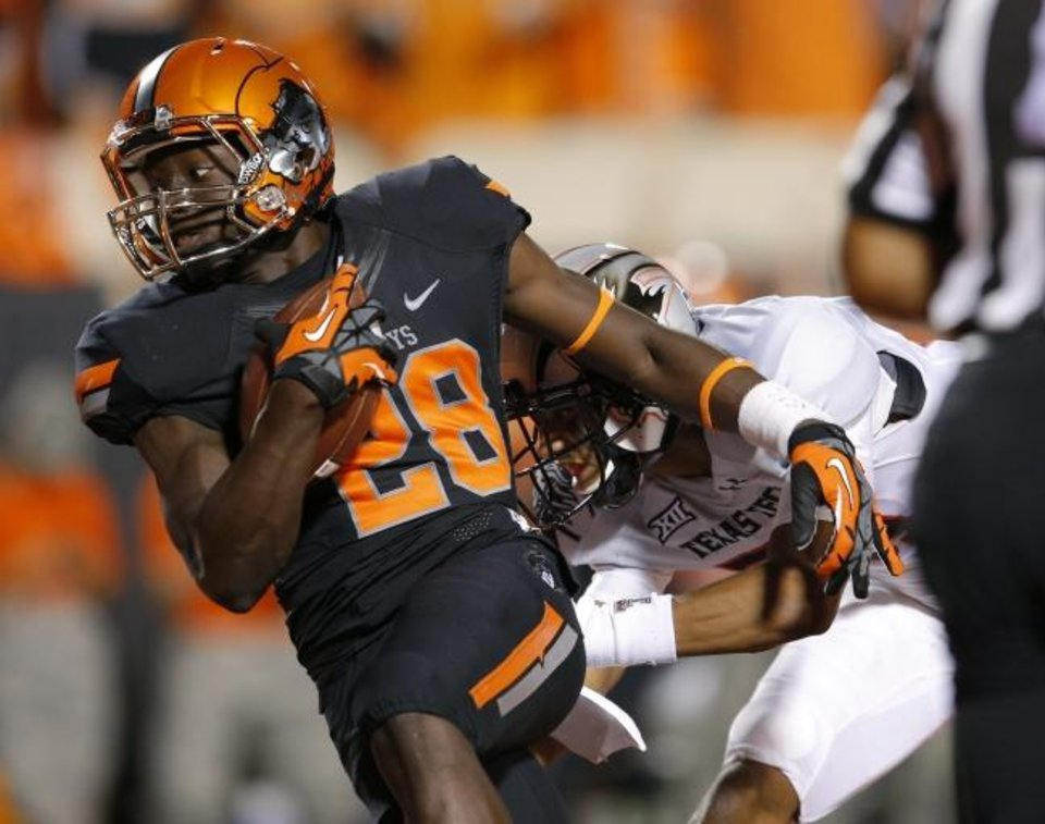 Photo -  The chrome orange helmets, first worn by OSU in 2014 against Texas Tech, make the combination with black jerseys and black pants the favorite for Oklahoman columnist Jenni Carlson. Cowboy receiver James Washington is seen wearing it here. [BRYAN TERRY/THE OKLAHOMAN]